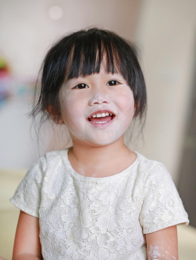 Portrait of cute little smile girl with baby powder on her face. Talcum concept stock images
