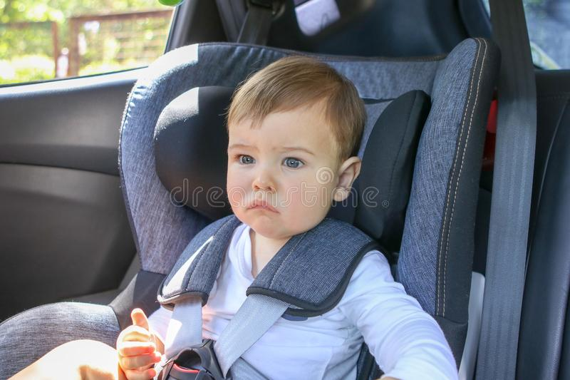 Portrait of cute little thoughtful baby sitting in the baby car seat looking forward. stock images