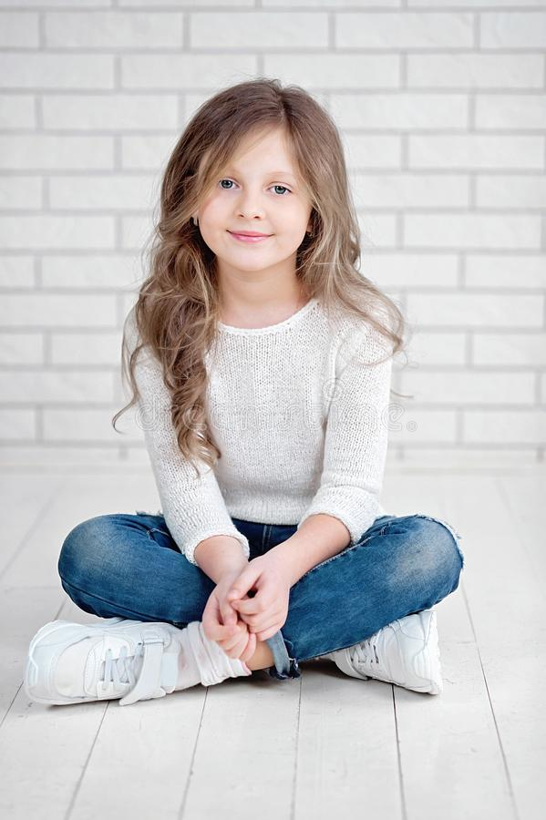 portrait of cute little 7 years old girl smiling and sitting on white wood floor in studio stock photography