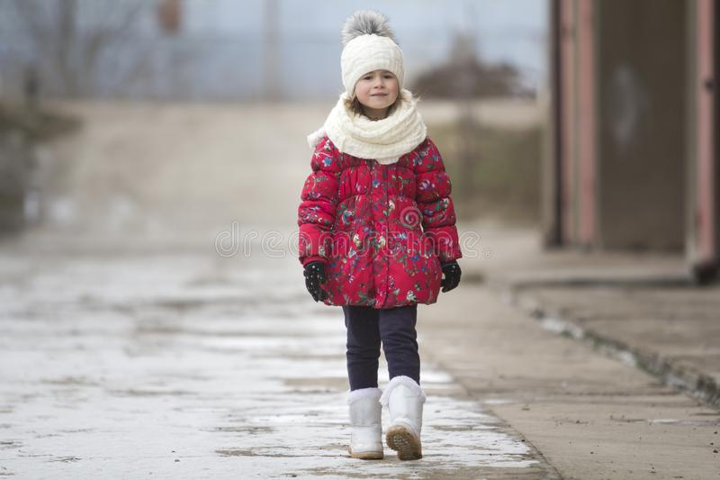 Portrait of cute little young funny pretty child girl in nice warm winter clothing walking confidently alone on white bright blurr stock photo