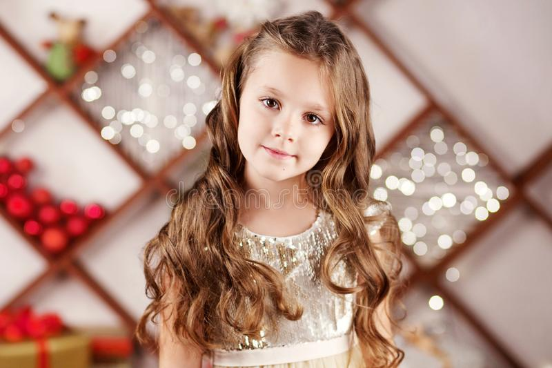 Portrait of a cute long-haired little girl in dress on background of Christmas lights. Christmas and New Year celebration concept. Winter holidays stock images