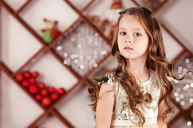 Portrait of a cute long-haired little girl in dress on background of Christmas lights. Christmas and New Year celebration concept. Winter holidays royalty free stock photos