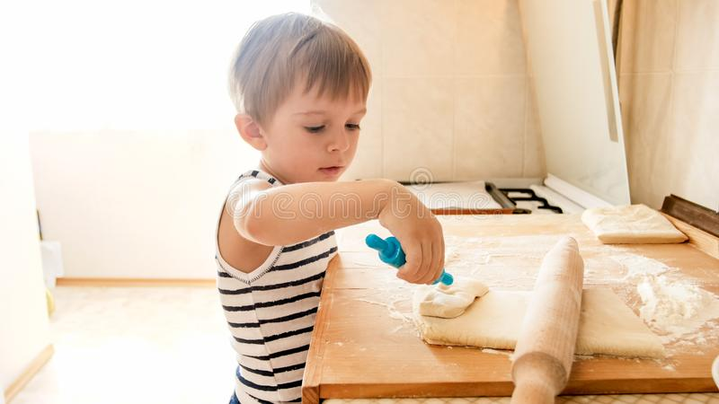 Portrait of little boy making dough on wooden kitchen counterboard. Child baking pies or cookies for nreakfast stock photography
