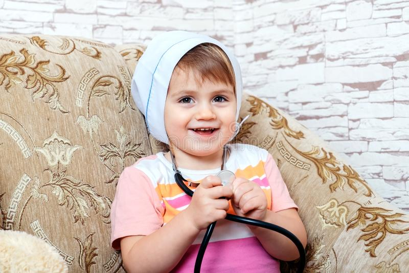 Portrait of cute miling child playing doctor or nurse with stethoscope royalty free stock images