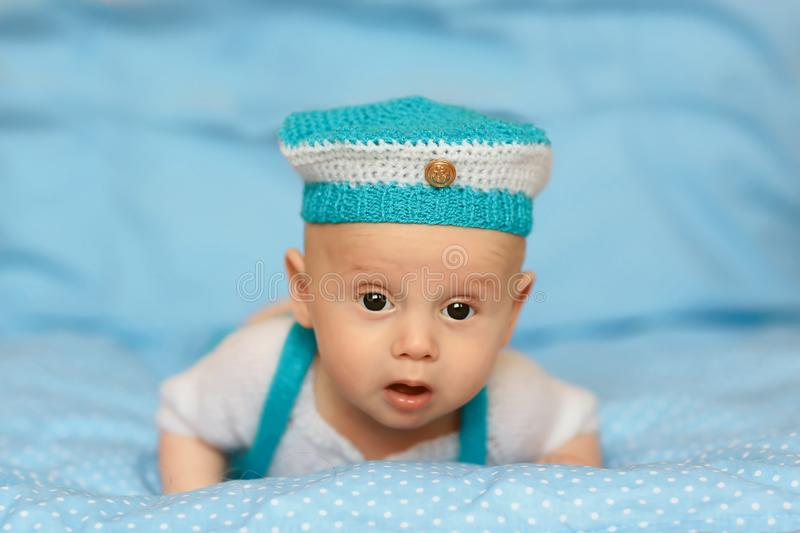 Portrait of a cute 3 months baby lying down in a blue hat on a blanket royalty free stock photography