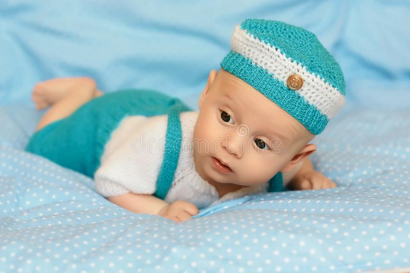 Portrait of a cute 3 months baby lying down in a blue hat in a blue suit on a blanket stock photography
