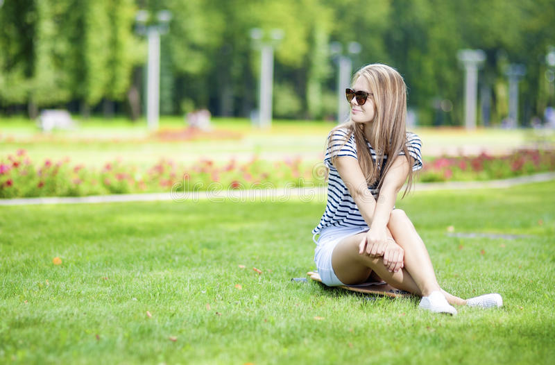 Portrait of Cute and Positive Caucasian Blond Teenager Girl Posing On Longboard in Green Summer Park stock photography