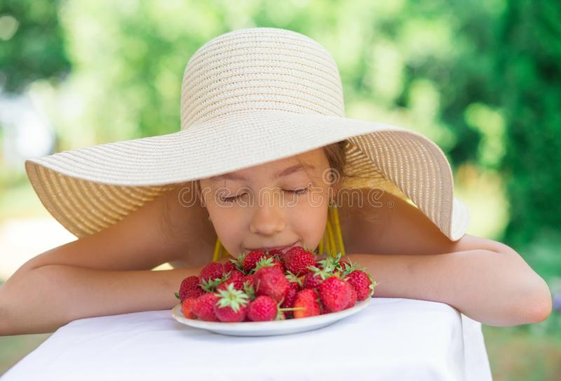 Portrait of Cute preteen girl in big hat is eating strawberries at summer day stock photography
