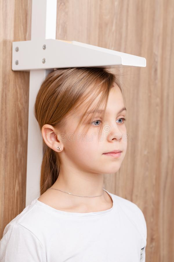 Child check up - measuring stature of preteen girl with stadiometer stock images