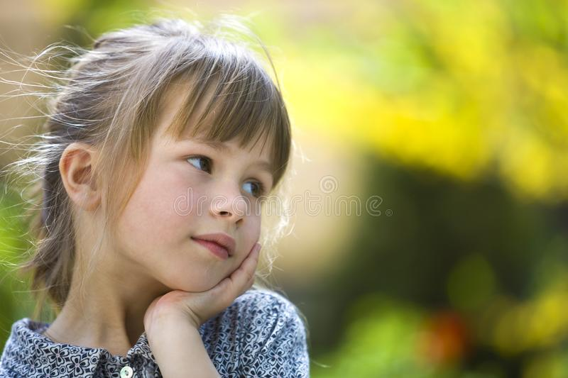 Portrait of cute pretty thoughtful child girl outdoors on blurred sunny colorful bright background royalty free stock photos