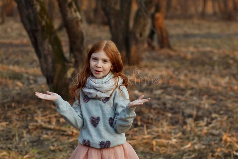 Portrait of a cute red-haired girl with freckles standing in an autumn or spring park or forest. Inspiration and dreams stock photo