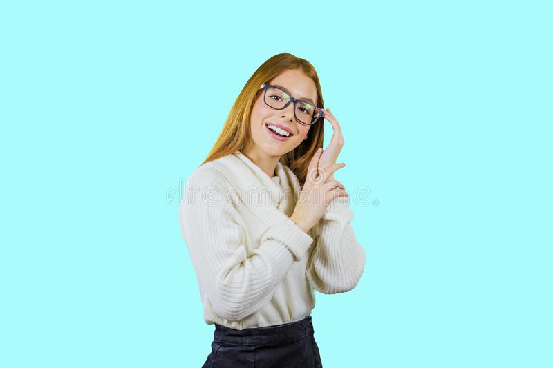 Portrait of a cute red-haired girl in glasses and a white sweater holding glasses with one hand and putting her other stock photo