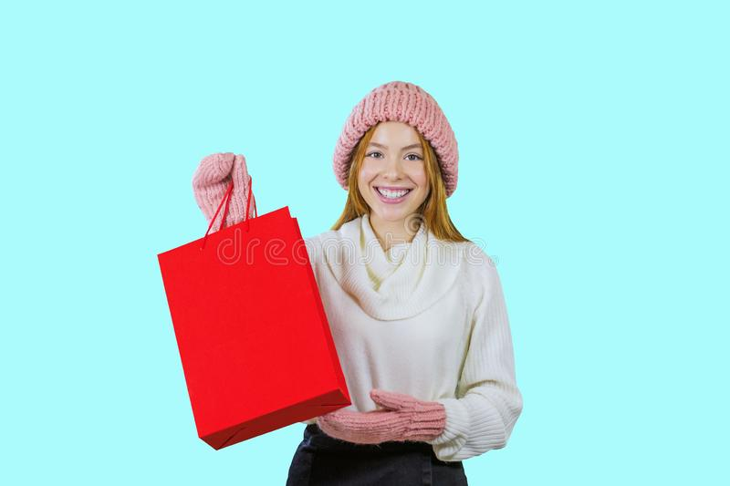 Portrait of a cute red-haired girl in a knitted hat and mittens holding a red bag and looking at the camera smiling royalty free stock images