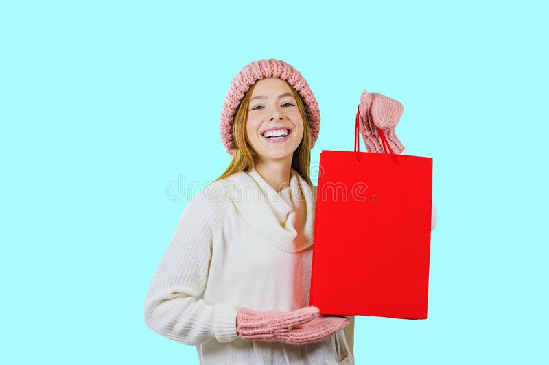 Portrait of a cute red-haired girl in a knitted hat and mittens holding a red bag and looking at the camera and laughing stock photo