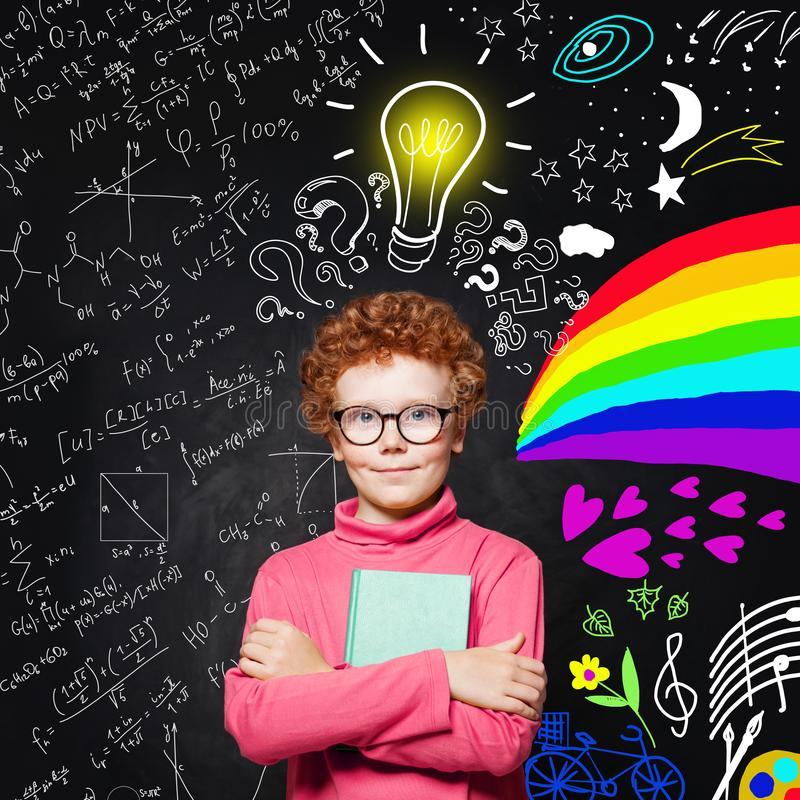 Portrait of cute redhead kid with light bulb. Curious child with colorful science and arts scetch. Kids education concept stock images