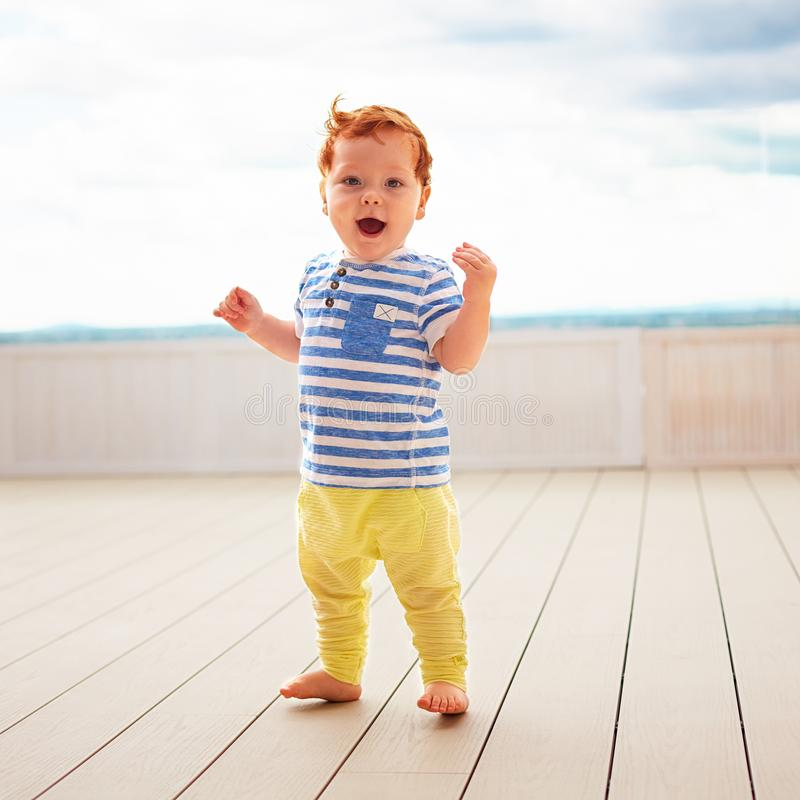 Portrait of cute redhead, one year old baby boy walking on decking stock photos