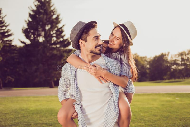 Portrait of cute romantic bearded brunet guy in checkered shirt, dreamy lady rides him on rear. Leisure, chill happiness, lawn st stock photos