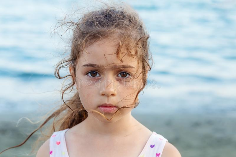 Portrait of cute sad little girl, standing at the seaside royalty free stock image