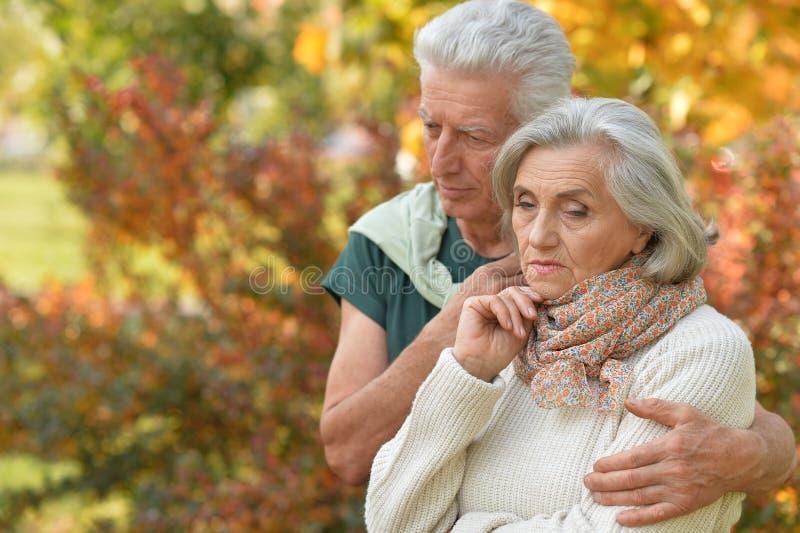 Portrait of cute sad senior couple in autumn park. Portrait of sad senior couple in autumn park royalty free stock photo