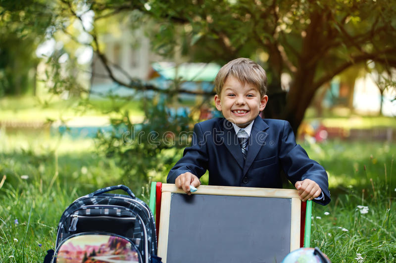 Portrait of cute school boy in the park, sunny day royalty free stock photo