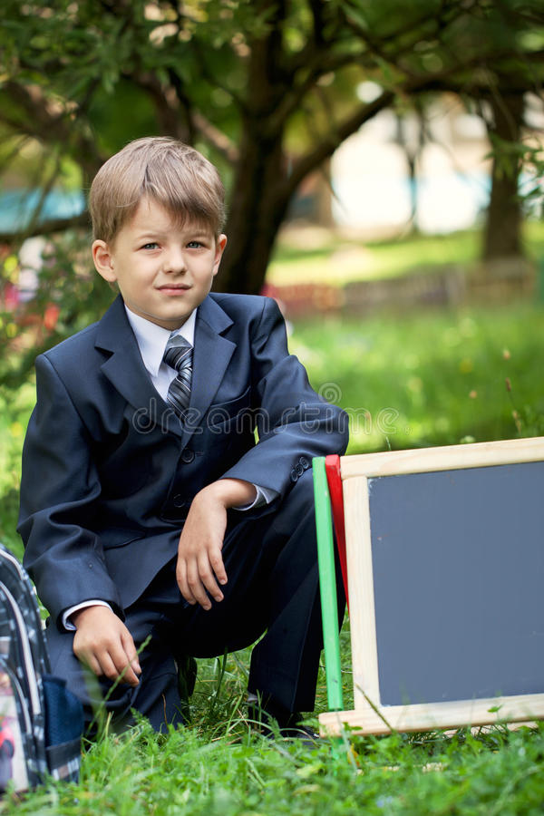 Portrait of cute school boy in the park, sunny day stock images