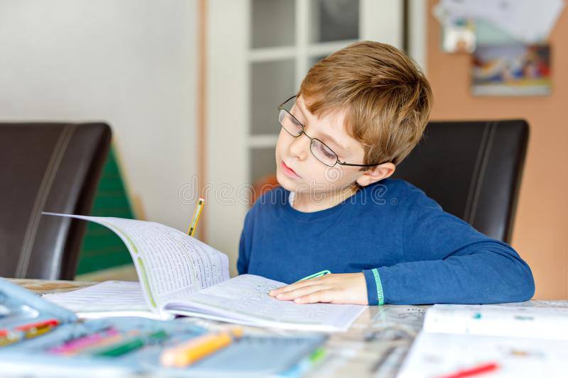 Portrait of cute school kid boy wearing glasses at home making homework. Little concentrated child writing with colorful. Pencils, indoors. Elementary school stock images