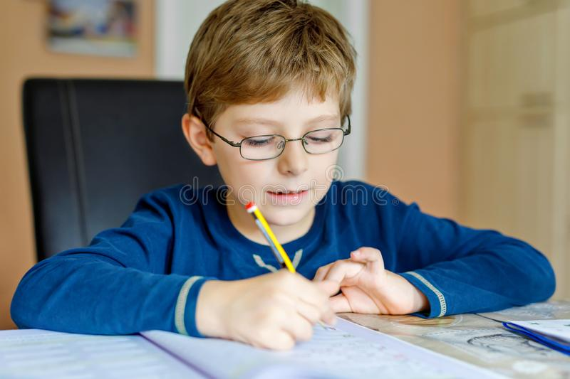 Portrait of cute school kid boy wearing glasses at home making homework. Little concentrated child writing with colorful. Pencils, indoors. Elementary school stock photo