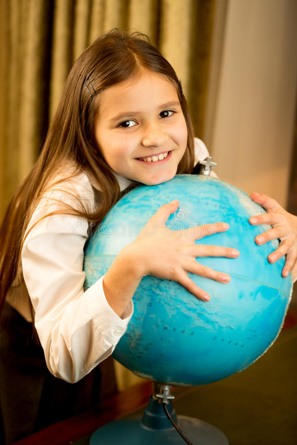 Portrait of cute schoolgirl holding Earth globe royalty free stock images