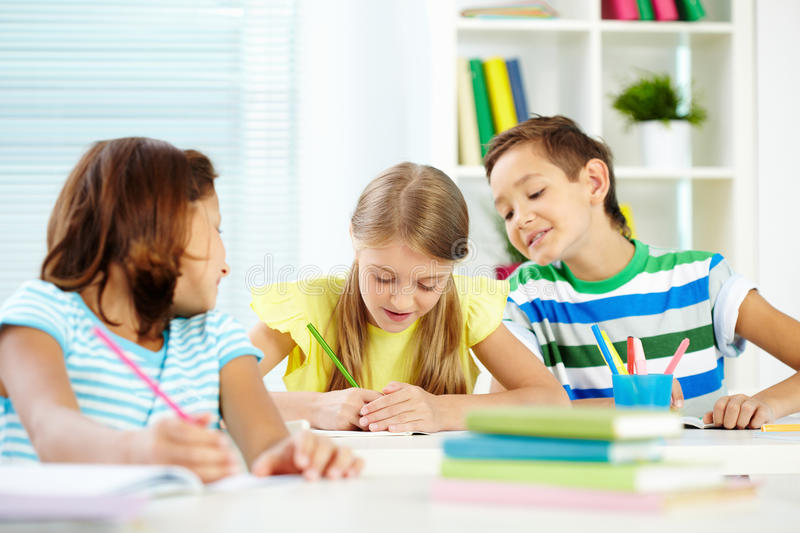 Drawing at lesson. Portrait of cute schoolkids drawing at lesson royalty free stock photo