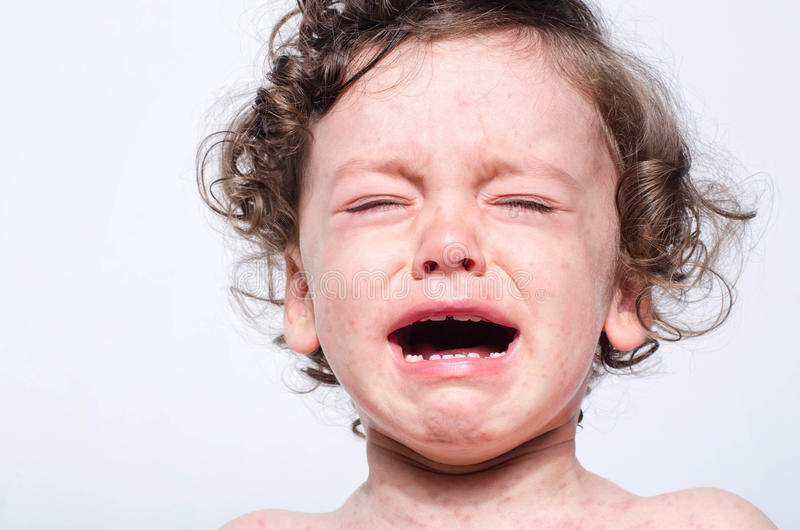 Portrait of a cute sick baby boy crying. Adorable upset child wi stock photo