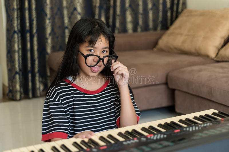 Portrait of the Cute silly young girl making funny faces, studding to play piano, looking at camera stock photos
