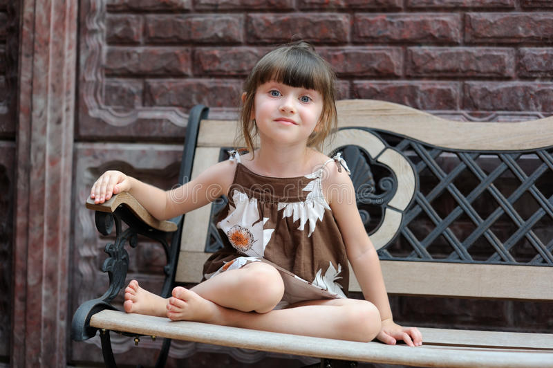 Portrait of cute smiling child sitting on bench royalty free stock photo