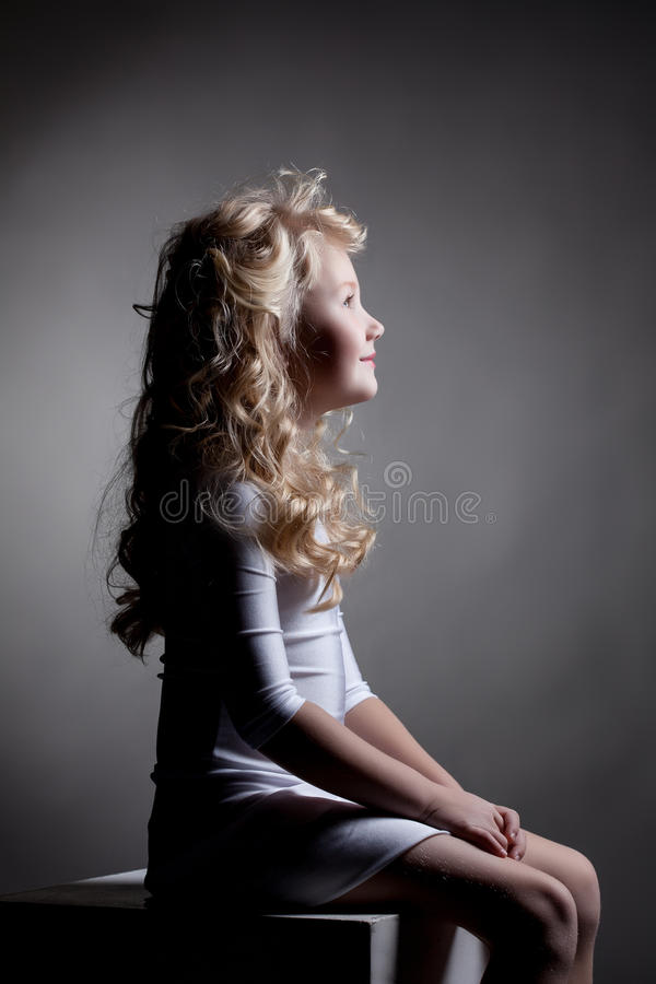 Portrait of cute smiling dancer sitting on cube royalty free stock photography