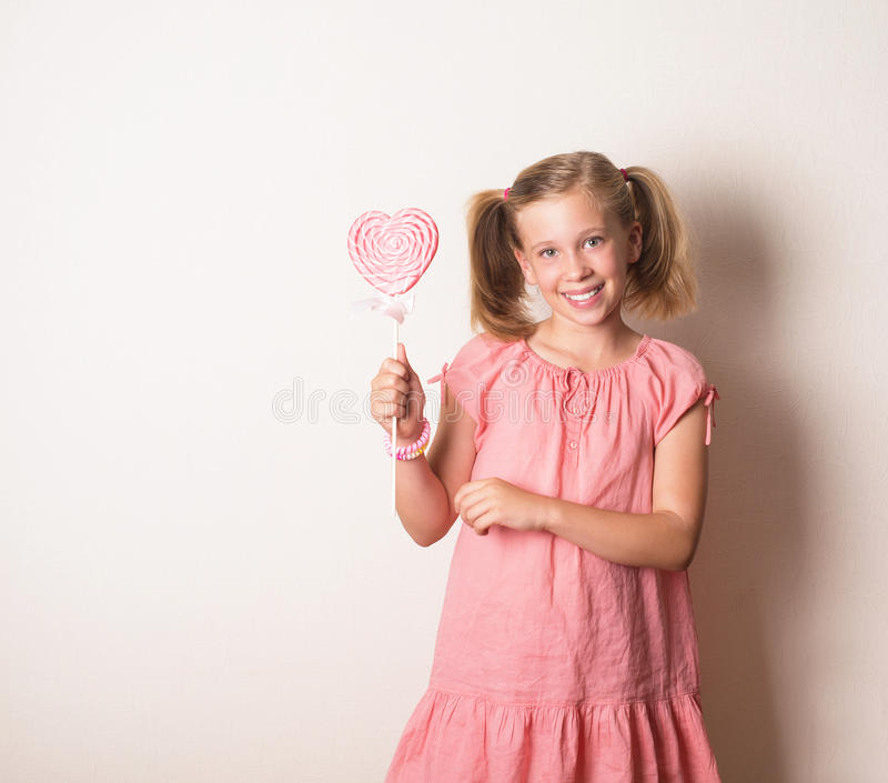Portrait of cute smiling girl with big heart shaped lollipop. Portrait of cute smiling girl in pink with big heart shaped lollipop stock images