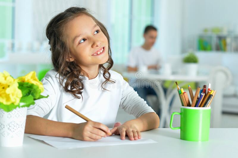 Portrait of a cute smiling girl drawing royalty free stock photography