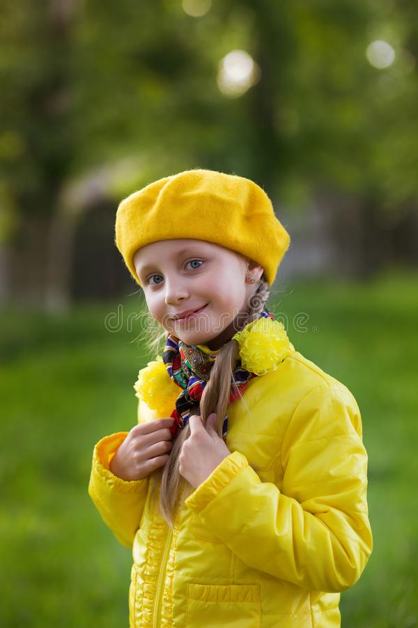 Portrait of a cute smiling girl in yellow clothes with pigtails in the spring park for a walk royalty free stock photos