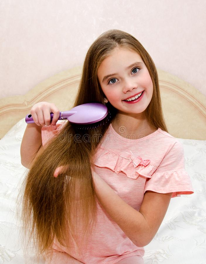 Portrait of cute smiling little girl child brushing her hair. Closeup stock image