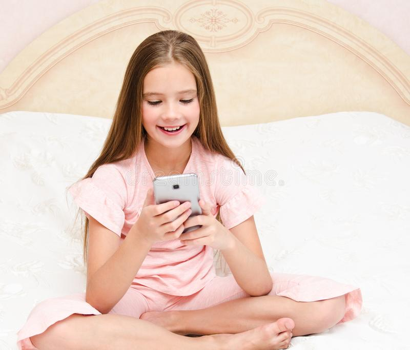 Portrait of cute smiling  little girl child playing with cell phone smartphone stock photos