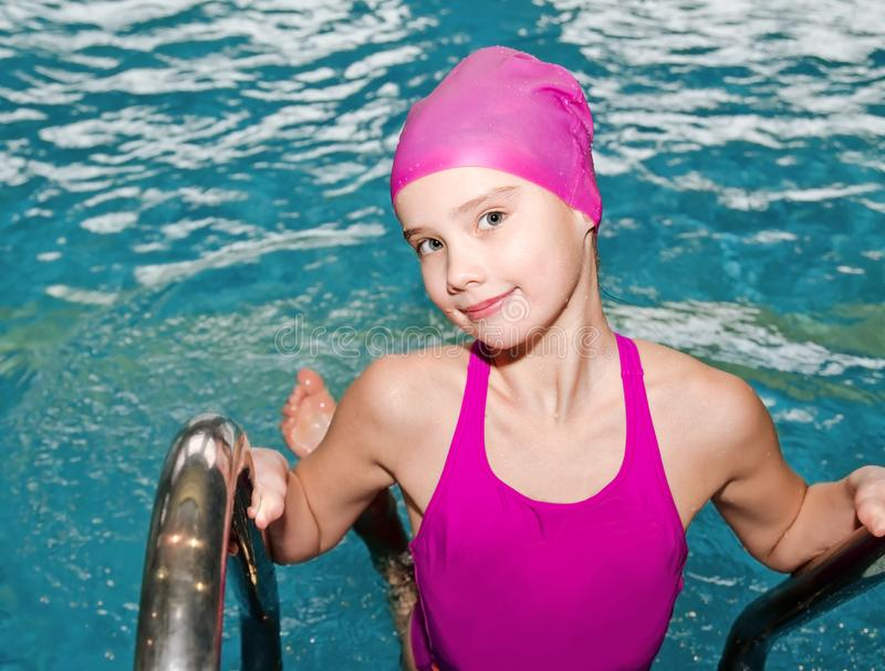 Portrait of cute smiling little girl child swimmer in pink swimming suit and cap in the swimming pool royalty free stock photo