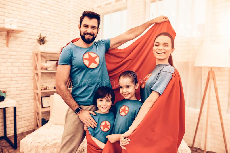 Portrait of Cute Smiling Super Hero Family at Home stock photo