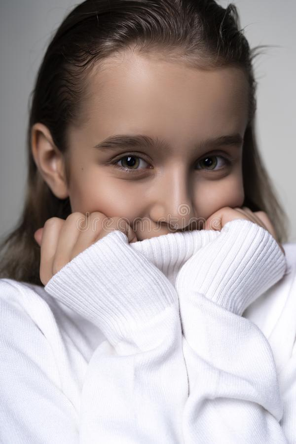 Portrait of a cute smiling teen girl wearing a white turtleneck sweater. Isolated on gray background. Advertising, trendy and stock image