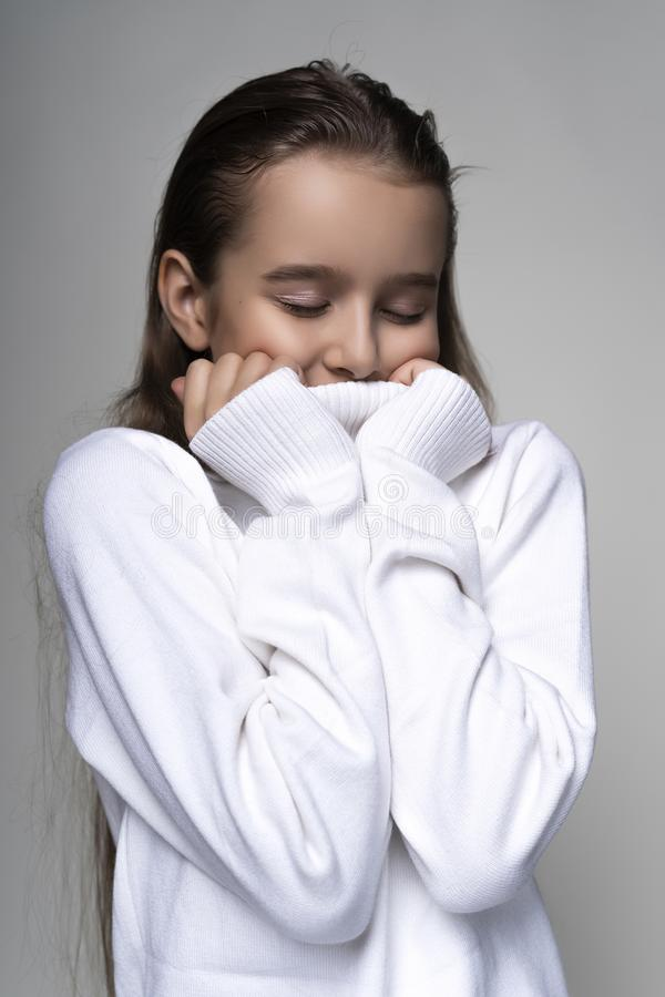 Portrait of a cute smiling teen girl wearing a white turtleneck sweater. Isolated on gray background. Advertising, trendy and royalty free stock photo