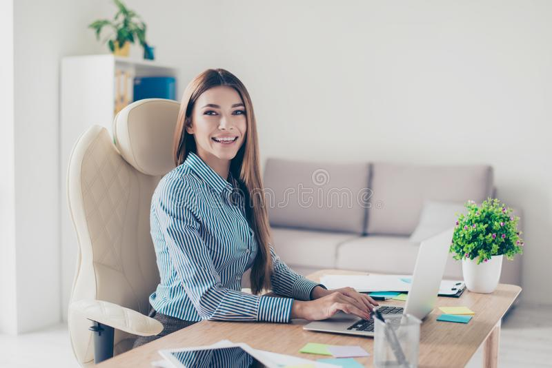 Portrait of cute smiling young business lady, sitting at her off. Ice and typing report royalty free stock photos