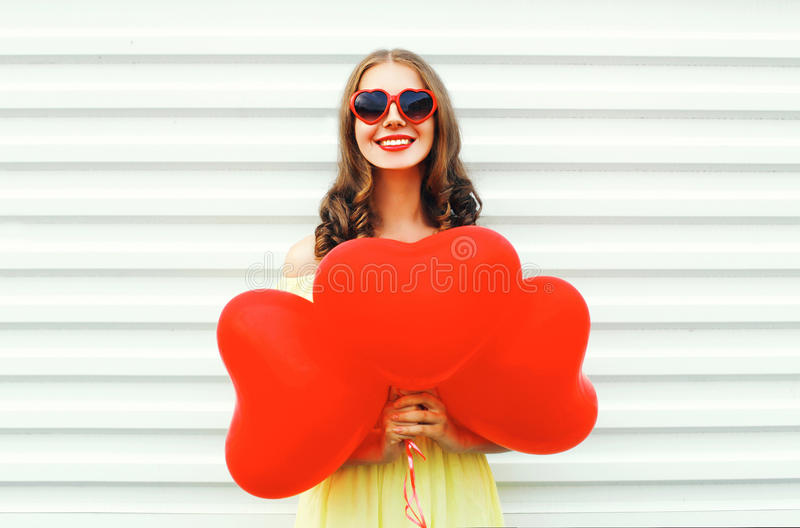 Portrait cute smiling young woman wearing red sunglasses with air balloons heart shape over white. Background stock photo
