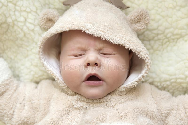 Portrait of a cute sneezing kid in a deer suit. Portrait of a cute sneezing blue-eyed kid in a deer suit royalty free stock photography