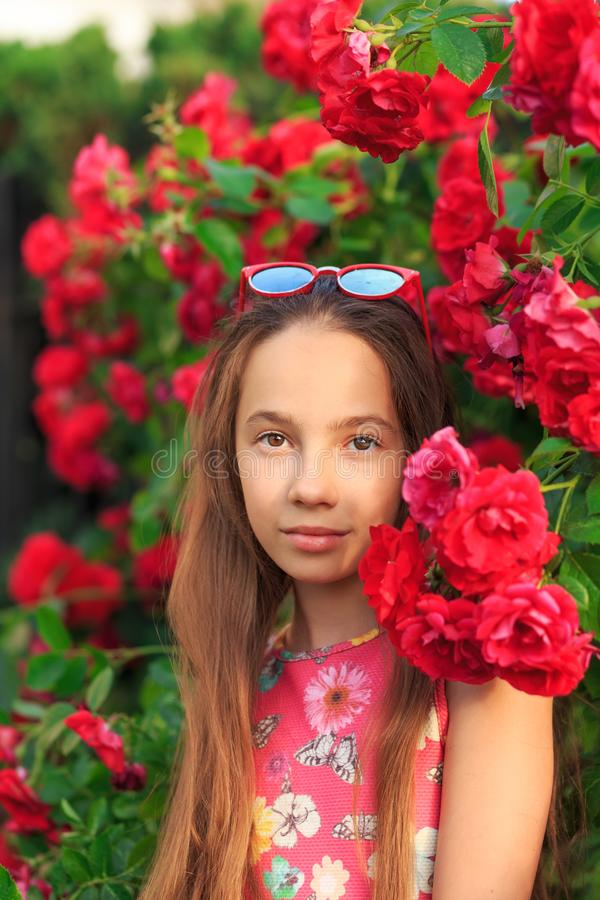 Portrait of cute teen girl smiling at the roses stock images