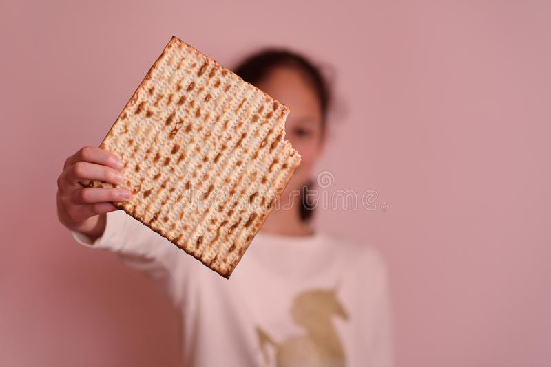 Young girl holding matzah or matza. Jewish holidays Passover invitation or greeting card.Selective focus.Copy space. stock images