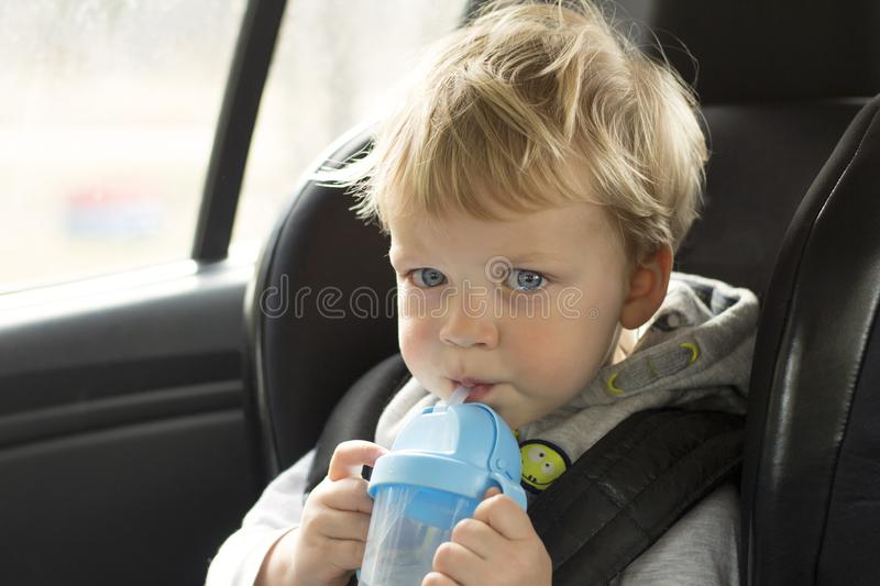 Portrait of cute toddler boy sitting in car seat. Child transportation safety. Adorable baby boy with water bottle stock image