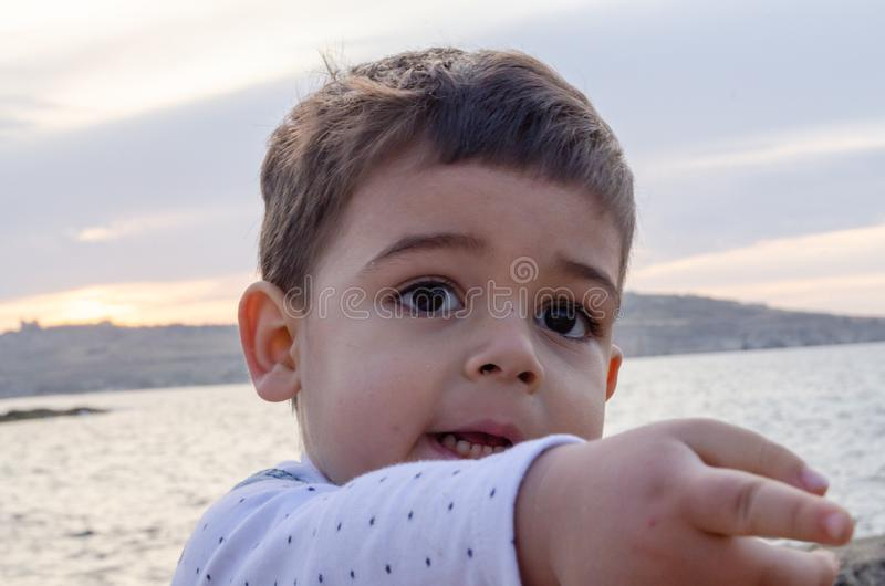 Portrait of cute two years old boy on the beach pointing finger to something close up stock images