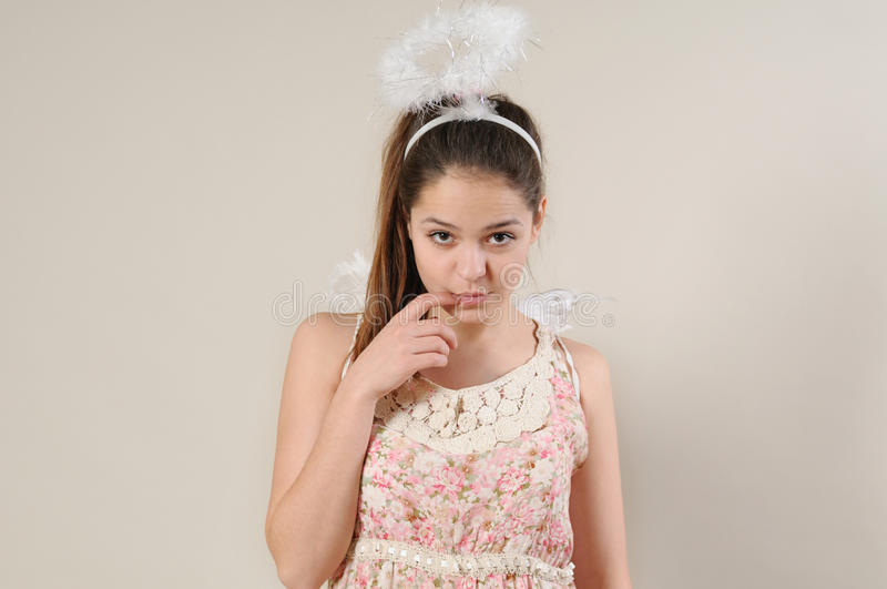 Portrait of cute very shy angel girl with finger near her mouth royalty free stock photography